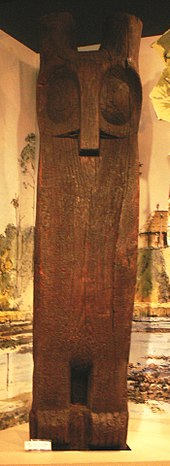 A tall, wooden figure representing an owl on display indoors