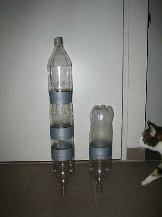 Water rocket - Two multi-bottle rockets with a cat for scale.