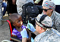 U.S. Air Force Maj. Curtis Hayes, left, and Senior Airman Britanni McKnight, right, both with the 86th Dental Squadron, examine a patient during Shared Accord 2013 in Mzantsi, South Africa, July 26, 2013 130726-A-ZZ999-023.jpg