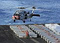 U.S. Navy sailors are poised to attach a sling to an approaching MH-60S Sea Hawk helicopter on the flight deck of the aircraft carrier USS John C. Stennis (CVN 74) during a weapons transfer 130418-N-YW024-281.jpg