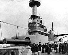 several men stand on deck next to a large turret, with a smaller one visible in the background
