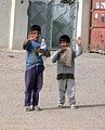 US Navy 030330-M-2176J-128 Two Iraqi boys wave at the passing Coalition Forces after receiving food and water.jpg