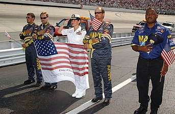 US Navy 040925-N-4729H-621 Lt. Heather Lichtenberg, center, Navy Career Counselor 1st Class Carlos Andrews, far right, and members of the Navy NASCAR pit crew stand in formation.jpg