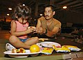 US Navy 050903-N-4374S-001 U.S. Navy Seabee, Construction Mechanic 1st Class Jesus Reyna, assigned to Naval Mobile Construction Battalion Seven (NMCB-7), takes time to eat lunch with his daughter.jpg