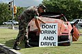 """US Navy 051130-N-7293M-003 U.S. Navy Master-at-Arms 1st Class Robert C. Tempesta places a """"Don't Drink and Drive"""" sign in front of a wrecked car outside the front gate of U.S. Naval Base Guam.jpg"""