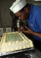 US Navy 070116-N-3688M-001 Culinary Specialist Seaman Devin Aikene prepares a cake in remembrance of Martin Luther King Jr., aboard USS Theodore Roosevelt (CVN 71).jpg
