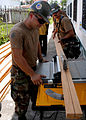 US Navy 070925-N-9406E-222 Sailors attached to Military Sealift Command hospital ship USNS Comfort (T-AH 20) cut boards to install safety banisters on a staircase at the Dorothy Bailey Municipal Centre.jpg