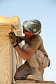 US Navy 081006-N-9623R-202 Builder 1st Class Scott Taylor works finishing the roof section on a South West Asia hut.jpg
