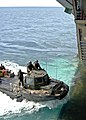 US Navy 090708-N-9950J-006 Sailors assigned to Assault Craft Unit One (ACU-1), Detachment Western Pacific (WESTPAC), guide a lighter amphibious re-supply cargo (LARC) vehicle into the well deck of the forward-deployed amphibio.jpg