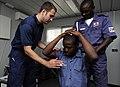 US Navy 100324-N-7948C-373 U.S. Coast Guard Maritime Law Enforcement Specialist Daniel Chase demonstrates proper personnel searching procedures to Nigerian and Ghanaian Sailors during a maritime law enforcement boarding officer.jpg