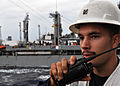 US Navy 101122-N-3620B-035 Boatswain's Mate 1st Class Justin Lacy communicates with the pilothouse aboard the amphibious transport dock ship USS De.jpg
