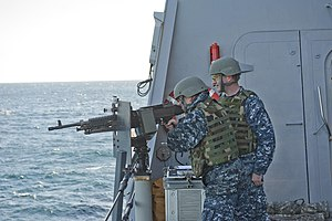 US Navy 120130-N-QM601-128 Fire Controlman 1st Class Kenny Ruth instructs Electronics Technician 3rd Class Eric Miravite on an M240 machine gun dur.jpg