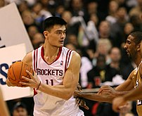 Yao Ming holding the ball on offense against t...