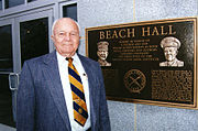 Elderly man in coat and tie standing next to a bronze dedication plaque located at the building entrance.
