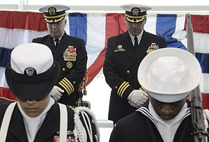 Destroyer squadron - Capt. Jeffrey Harley, Commander Destroyer Squadron Nine (DESRON 9), left, and Cmdr. Jonathan Christian, Commodore Afloat Training Group Pacific Northwest, right, bow their heads during the invocation at the beginning of the change of command ceremony held for Afloat Training Group Pacific Northwest in the Grand Vista Ballroom at Naval Station Everett.