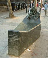 tek Wilde ile görüşmesinde olmanın yaşamaya straddles koltukta diğer az bir yükseltilmiş ucuna yerleşik Wilde'ın yüzü büstüne ile düşük dikdörtgen kamu anıt.