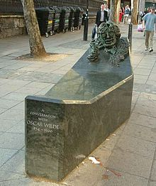 A low rectangular public monument, with a bust of Wilde's face built into one raised end, at the other at seat that one straddles to experience being in conversation with Wilde.