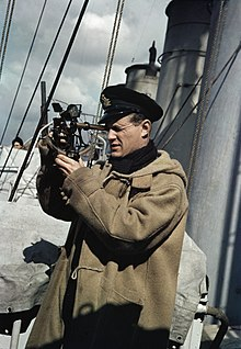 Un officier de la Royal Navy utilisant un sextant, à bord d'un destroyer en mission de protection d'un convoi en 1942.