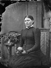 A young woman sitting and holding a flower