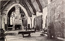 A monochrome photograph of a grand living room with a 36-foot-high arched ceiling, a high fireplace, and tall stained glass windows.