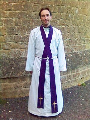 Girdle - An Anglican Christian priest wearing a white girdle around his waist to hold his alb and stole in place.