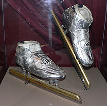 Metallic silver skates with golden blades in a glass case with the right skate being slightly elevated.  There is a burgundy curtain behind the skates.  The blades are much longer than the actual boot of the skates.
