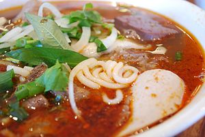 Vietnamese cuisine - Bún bò Huế, a spicy, lemongrass rice vermicelli noodle soup served with fresh herbs and vegetables