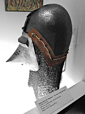 "Bascinet - Bascinet with an aventail and ""klappvisor"". The method of fixing the aventail to the helmet, via a pierced leather band fitted over rivets on the  helmet (vervelles) secured by a cord passing through the vervelles, is shown"