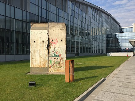 The fall of the Berlin Wall, a section of which is now displayed outside NATO Headquarters, marked a turning point in NATO's role in Europe. Berlin Wall at NATO Headquarters.jpg