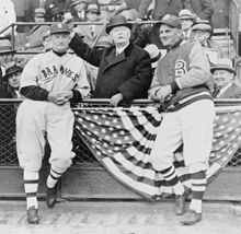 At a baseball stadium, two men in baseball uniforms stand on the field, flanking a well-dressed man who pantomimes throwing a baseball.