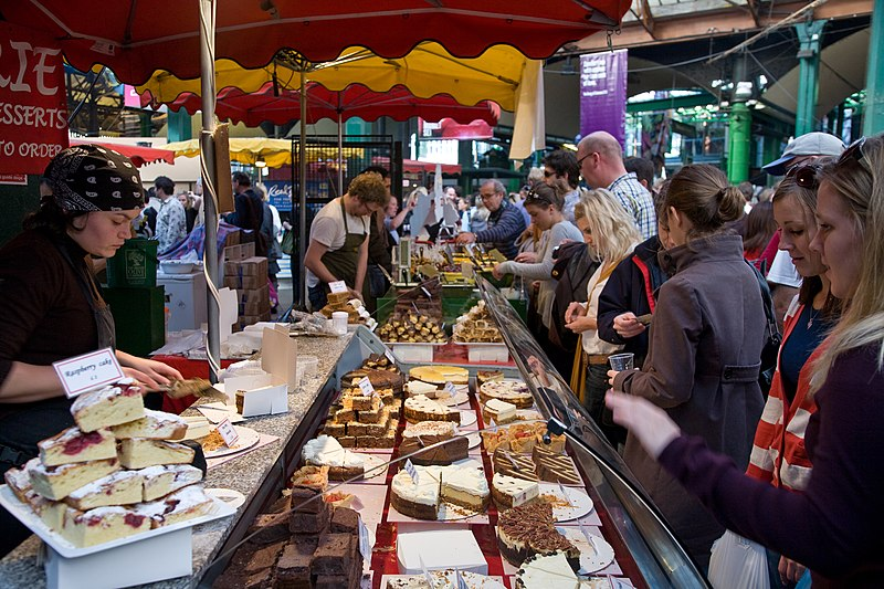 A cake stall in busy Borough Market on a Saturday afternoon in London, England