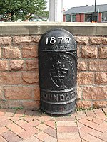 A black cast-iron half-round post with a domed top. Around one metre high. It has the year '1877' in white raised lettering. It also says 'CITY OF NOTTINGHAM' in capital letters which is accompanied with the coat of arms of the City of Nottingham, and the word 'BOUNDARY' in capital letters below that.
