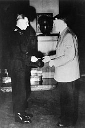 Wittmann, standing on the left, is shown receiving his Knight's Cross of the Iron Cross from Adolf Hitler standing on the right.