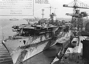 "Graf Zeppelin-class aircraft carrier - The Graf Zeppelin at Kiel, June 1940, displaying her newly rebuilt bow. Also visible are her 15 cm casemate guns, before their removal to defend occupied Norway. The photo is marked Geheim (""secret"")."