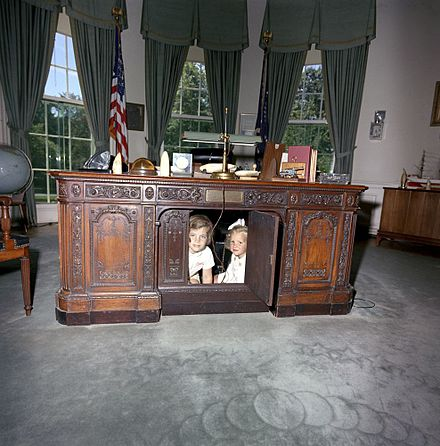Caroline Kennedy and Kerry Kennedy beneath the Resolute desk in 1963 Caroline Kennedy Kerry Kennedy Resolute Desk a.jpg