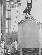 Large conical structure on a pulley with a man on top and two near the base.