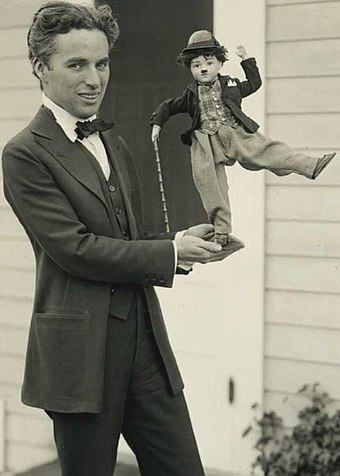 By 1916, Chaplin was a global phenomenon. Here he shows off some of his merchandise, c. 1918. Charlie Chaplin with doll.jpg