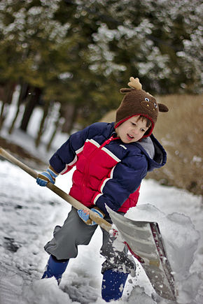 A child in appropriate clothing, moving a shovelful of fresh snow