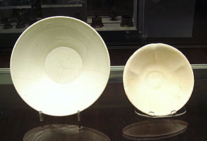 Tin-glazing - Chinese porcelain white ware bowl (left) found in Iran, and Iraqi tin-glazed earthenware bowl (right) found in Iraq, both 9-10th century, an example of Chinese influences on Islamic pottery. British Museum.