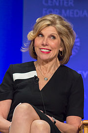 A blonde woman wearing a black dress smiles as she looks to her left away from the camera