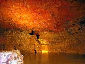 Clearwell Caves - Pool of water within the mine. Note the red ochre colour of the roof