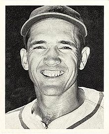 A smiling man in a white baseball uniform with dark trim going around the neck and a dark cap.