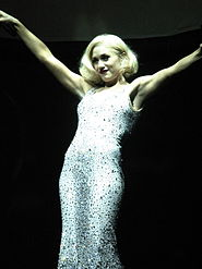 A blonde woman is standing with her arms up. She is wearing a long platinum dress that is adorned with jewellery, the background is black.