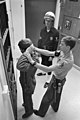 Corporal Thomas, on shore patrol duty, prepares to put handcuffs on an unauthorized absentee serviceman as Master-At-Arms 1st Class Getman stands by DM-SN-85-02410.jpg