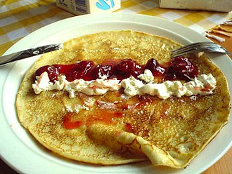 Crêpe - A sweet crêpe opened up, with whipped cream and strawberry sauce on it.