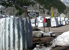 Large blocks of partially worked white marble lie on the ground at Colorado's Marble Mill site with the National Historical marker in the background.
