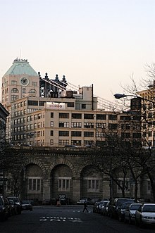 A stone viaduct approach ramp to the Brooklyn Bridge, as seen from a street in Brooklyn, with buildings to either side