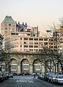 Eine steinerne Viadukt-Zufahrtsrampe zur Brooklyn Bridge, von einer Straße in Brooklyn aus gesehen, mit Gebäuden zu beiden Seiten
