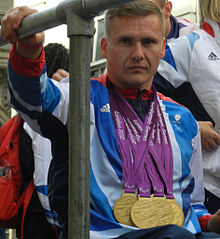 A man in a wheelchair, he wears a white and blue top and around his neck hang four gold medals.
