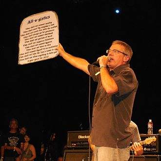 """All (Descendents album) - Since 1987 it has been common for Aukerman to hold up a sign displaying the """"All-O-Gistics"""" when performing the song, as seen here in 2014."""